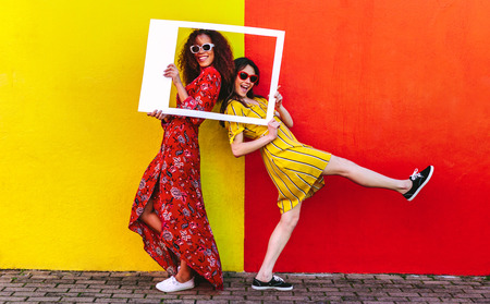 Two women friends with blank photo frame standing against colored wall outdoors. Female travelers posing at camera with empty picture frame. Stockfoto