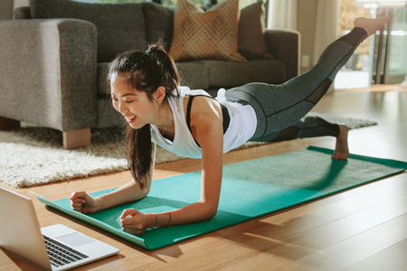 Smiling woman exercising at home and watching training videos on laptop. Chinese female doing planks with a leg outstretched and looking at laptop. Stock Photo