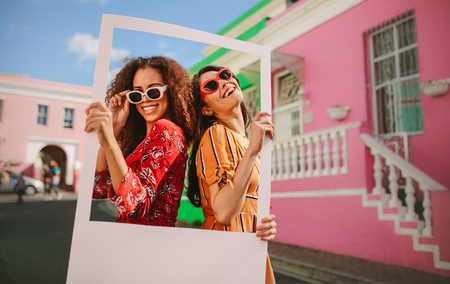 Two women wearing colourful dress and sunglasses standing outdoors holding a photo frame with houses in background. Beautiful female friends enjoying outdoors with a blank picture frame.