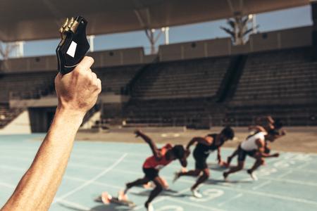 Nahaufnahme der Hand, die eine Starterpistole abfeuert, um das laufende Rennen zu starten. Athleten starten für ein Rennen auf einer Laufstrecke. Standard-Bild