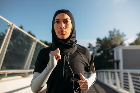 Gesunde sportliche Frau mit Hijab Joggen im Freien in der Stadt. Islamische Frau, die früh morgens läuft.