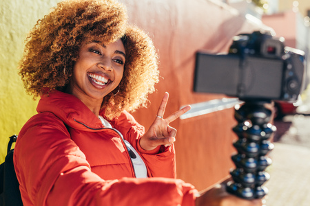 Smiling afro american woman traveller taking a selfie using her digital camera. Smiling female tourist recording content for her blog outdoors holding a dslr camera showing victory symbol. Foto de archivo