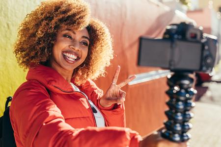 Sorridente donna afroamericana viaggiatrice prendendo un selfie usando la sua macchina fotografica digitale. Sorridente turista femminile che registra contenuti per il suo blog all'aperto con in mano una fotocamera reflex digitale che mostra il simbolo della vittoria. Archivio Fotografico