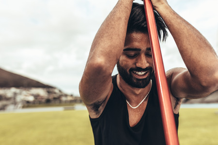 Smiling athlete relaxing during his javelin training standing in the field holding a javelin. Close up of an athlete standing in a stadium training holding a javelin. Foto de archivo - 116072522