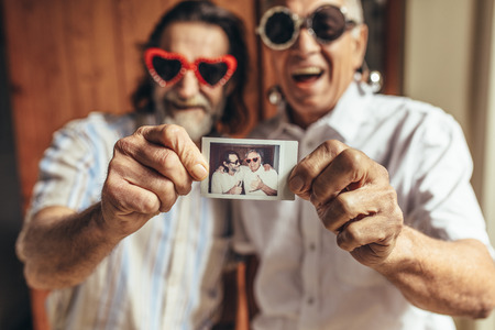 Two elderly male friends with party sunglasses showing their picture. Senior people having great time together. Focus on picture in hand of old people.
