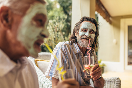Two senior friends with facial clay mask on drinking juice. Retired men sitting together with face mask having juice.