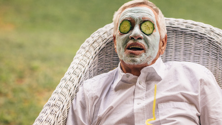 Retired man sitting on chair with clay facial mask and cucumber slice on face. Senior man taking facial spa treatment.