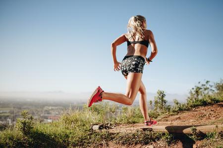 Vista posteriore di una donna in sprint abbigliamento fitness. Atleta femminile che si allena all'aperto in esecuzione in una giornata di sole.