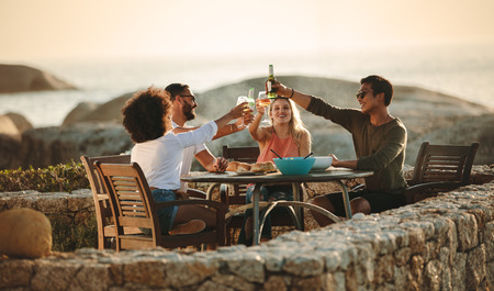 Four friends toasting drinks sitting on a dining table outdoors near the seashore. Multiethnic friends on a holiday having fun drinking wine and snacks. Stockfoto