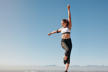 Fitness woman doing workout standing on a hill listening to music. Cheerful woman in fitness wear doing workout outdoors with clear blue sky in the background. Imagens