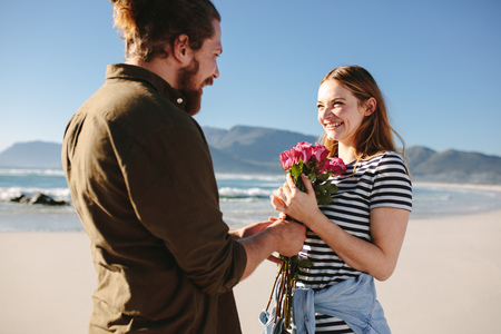 Man giving surprise bouquet of roses to beautiful woman on the beach. Man surprising girlfriend on a romantic date. Couple in love on beach.