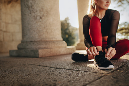 Woman in fitness wear sitting on ground and tying her shoelace. Fitness woman tightening her shoes during workout.