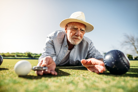 Senior person checking the distance between a boules and the jack for the result. Stock Photo