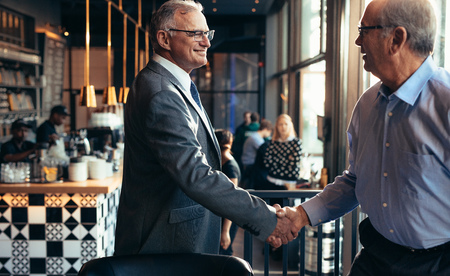 Senior businessman shaking hands to a man in restaurant.