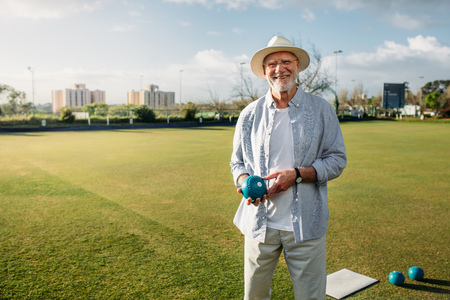 Smiling old man standing in a park with a boules in hand. Stock Photo