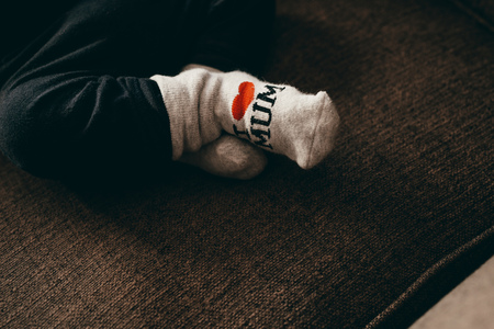 Baby wearing socks with I love mum written on it.