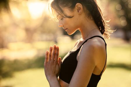 Fitness-Frau, die Yoga mit ihren Händen macht, verbunden und die Augen geschlossen Standard-Bild