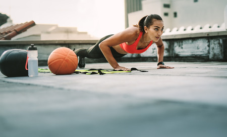 Woman athlete doing push ups on the rooftop with medicine ball and basketball by her side.