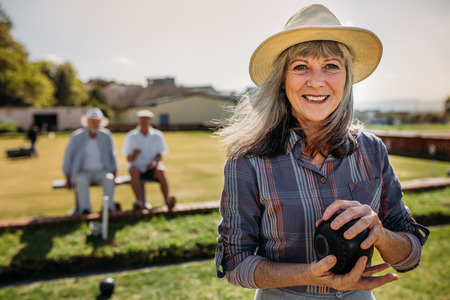 Smiling senior woman in hat standing in a lawn holding a boules.