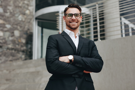 Smiling businessman standing outdoors with arms crossed.