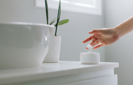 Close up of female hands taking moisturizing cream from bottle in bathroom. Banque d'images