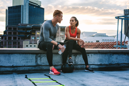 Man and woman in fitness clothes relaxing on the rooftop during workout.