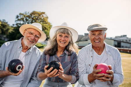 Smiling senior people sitting in a lawn holding boules. Stock Photo