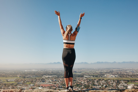 Woman in fitness wear standing on the edge of a hill looking at the city below.