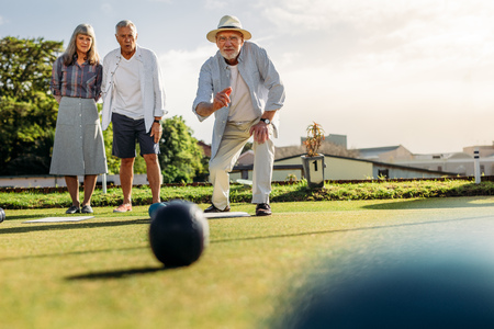 Senior man in hat throwing a boules while his friends look on. Stock Photo