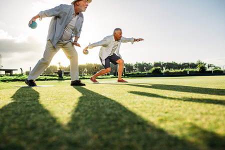 People playing a game of boules in a lawn with sun