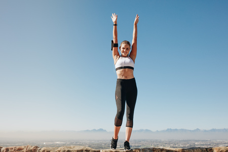 Female athlete standing on a hill and doing workout while listening to music.