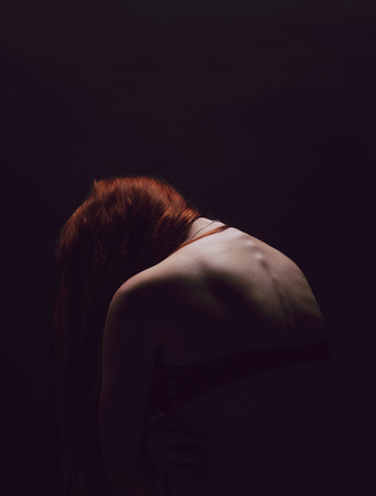 Rear view of very thin redhead woman being ashamed of her body. Underweight female feeling sad over dark background.