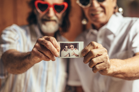 Two retired men showing their old photograph. Senior friends with a picture in hand. Focus on hand holding a photograph. 스톡 콘텐츠
