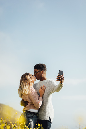 Loving interracial couple kissing and taking self portrait outdoors. Romantic couple taking selfie with their mobile phone. Imagens