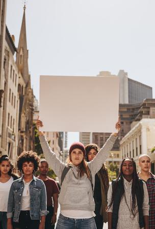 Gruppo multirazziale di femmine che protestano all'aperto sulla strada. Femmina con il gruppo che tiene la bandiera in bianco durante una protesta.