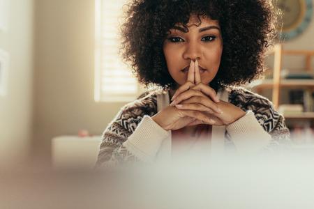 Femme africaine aux cheveux bouclés assise à son bureau et pensant. Portrait d'une travailleuse réfléchie au bureau à domicile. Banque d'images