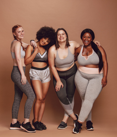 Group of women of different race, figure type and size in sportswear standing together over brown background. Diverse women in sports clothing looking at camera and laughing. Фото со стока