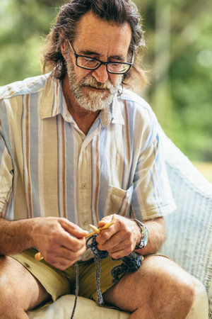Senior man with beard knitting while sitting on chair. Old man knitting with needles and wool yarn.