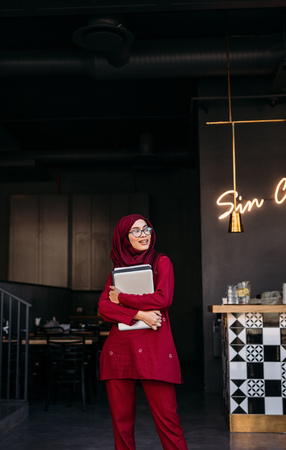Woman in hijab grabbing laptop with both hands and looking away while standing at cafe. Islamic woman standing at coffee shop door with laptop in hand.