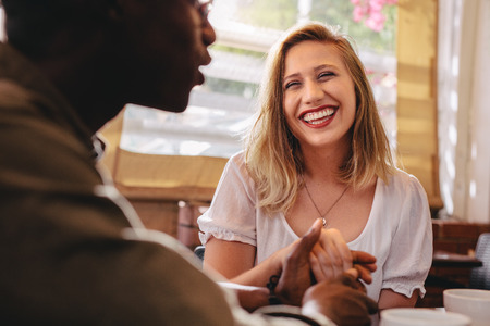Happy young woman holding hand of her boyfriend at coffee shop. Loving couple on a date at cafe. Stock Photo