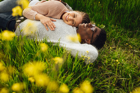 Beautiful young couple lying in green grass outdoors. Young man and woman lying in the flowering meadow outdoors.