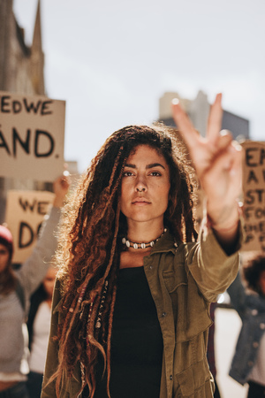 Female activist with peace sign at women's march. Woman leading a protest on road. Stock Photo