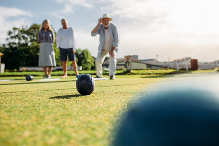 Old man in hat throws a boules standing in position in a lawn with his friends standing behind in background. Group of senior people playing boules in a park. Stok Fotoğraf
