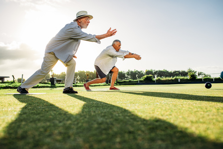 Two senior men throwing boules in a park with their shadows falling on the ground. Elderly men enjoying a game of boules in a lawn on a sunny day. Stock Photo
