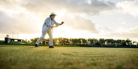 Old gentleman in hat in position to throw a boules in a lawn. Man playing boules in a playground with sun flare in the background.