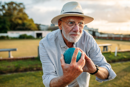 Close up of an old man in hat holding a boules ready to throw. Senior man playing a game of boules in a park.