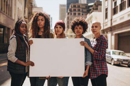 Gruppo di manifestanti femmine sulla strada con un cartello bianco. Femmine che tengono striscione bianco durante una protesta.