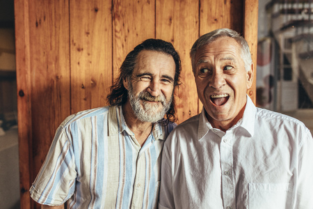 Two crazy senior friends standing together making funny faces. Retired men having fun together at home.