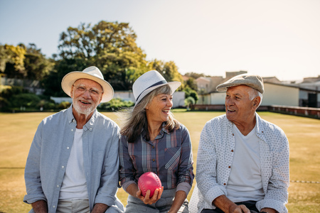 Senior woman sitting with her male friends with a boules in hand. Old friends sitting together on a bench in a park and talking.