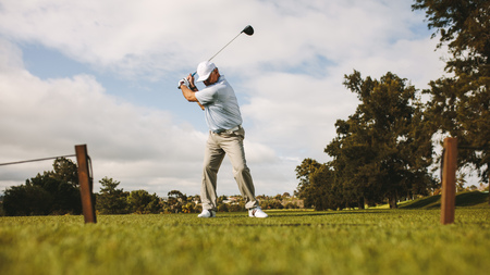 Low angle shot of senior male golfer taking shot while standing on field. Full length of golf player swinging golf club. Stock Photo